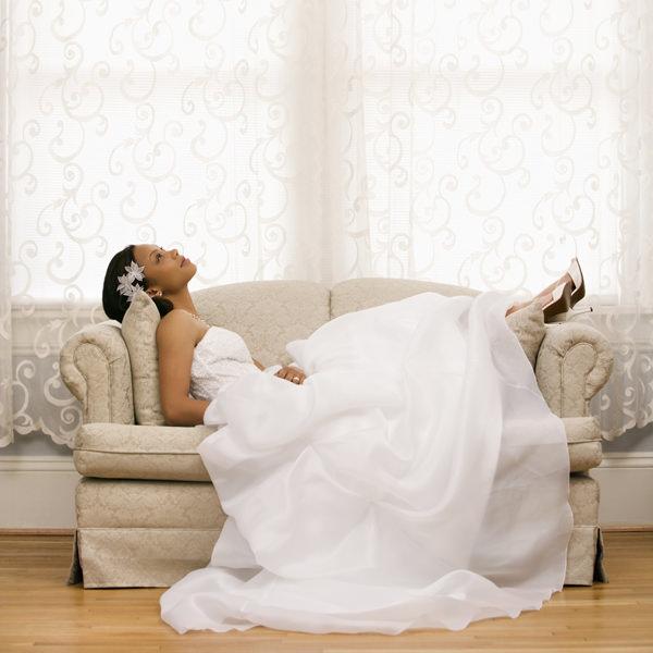 Braut liegt mit dem Rücken auf einem Sofa