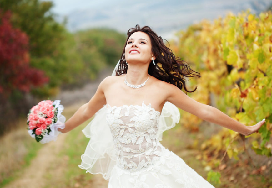 Braut mit Blumenstrauß vor einem Feld